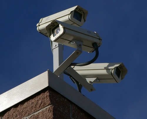 Three security cameras on a roof.