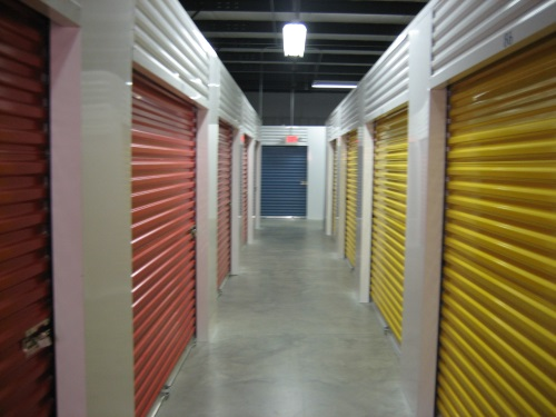 A well lit hall way in a self storage facility.