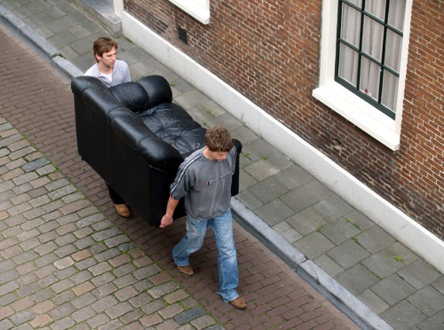 Two friends moving a couch.