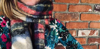 Women in scarf and jacket against brick wall