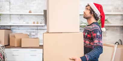 man lifting boxes with a christmas sweater and santa hat, used for winter packing tips | Forney