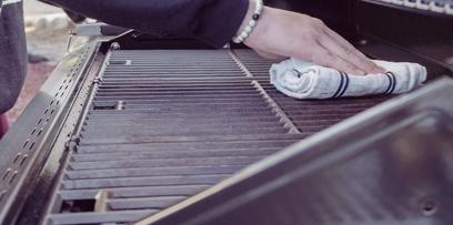 A man cleans a grill before storage