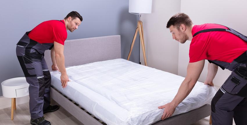 Two professional movers lifting a bed