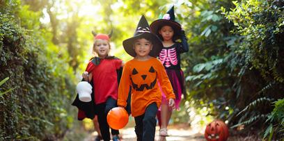 Three kids in Halloween costumes trick-or-treating